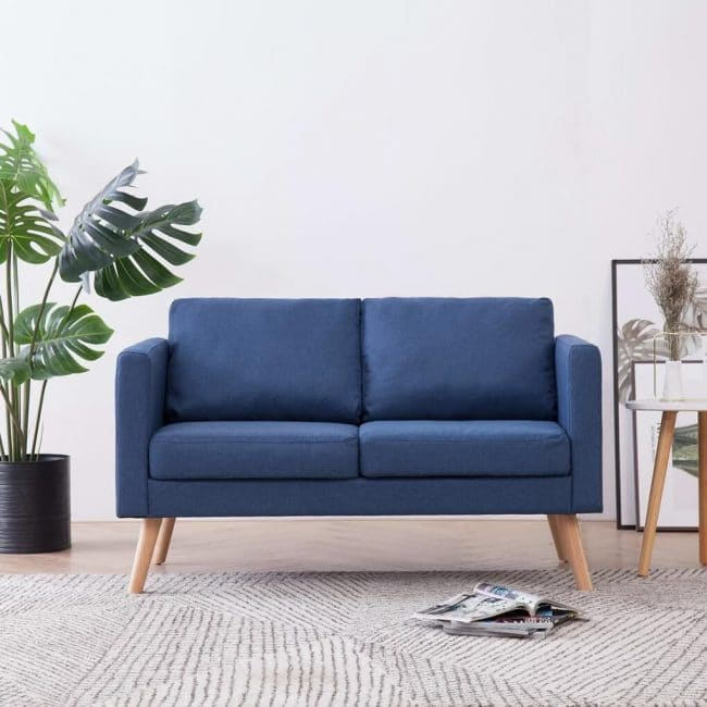 Modrá pohovka v obývacím pokoji s látkovým potahem ve skandinávském stylu